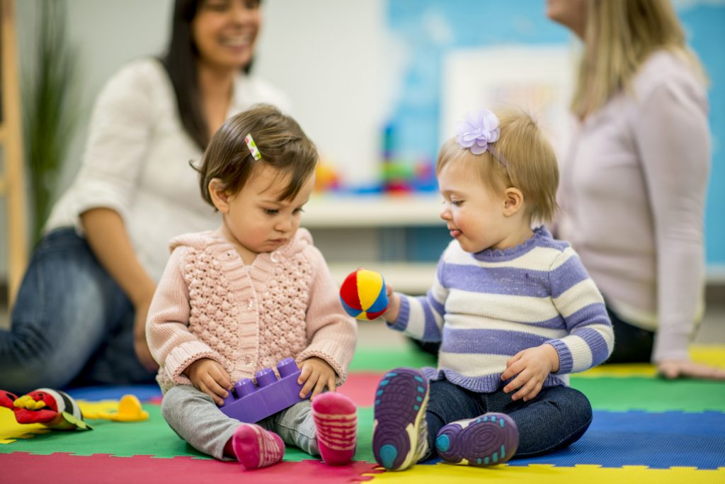 A multi-ethnic group of babies, their mothers in the background, playing together with toys in a daycare / preschool setting.
